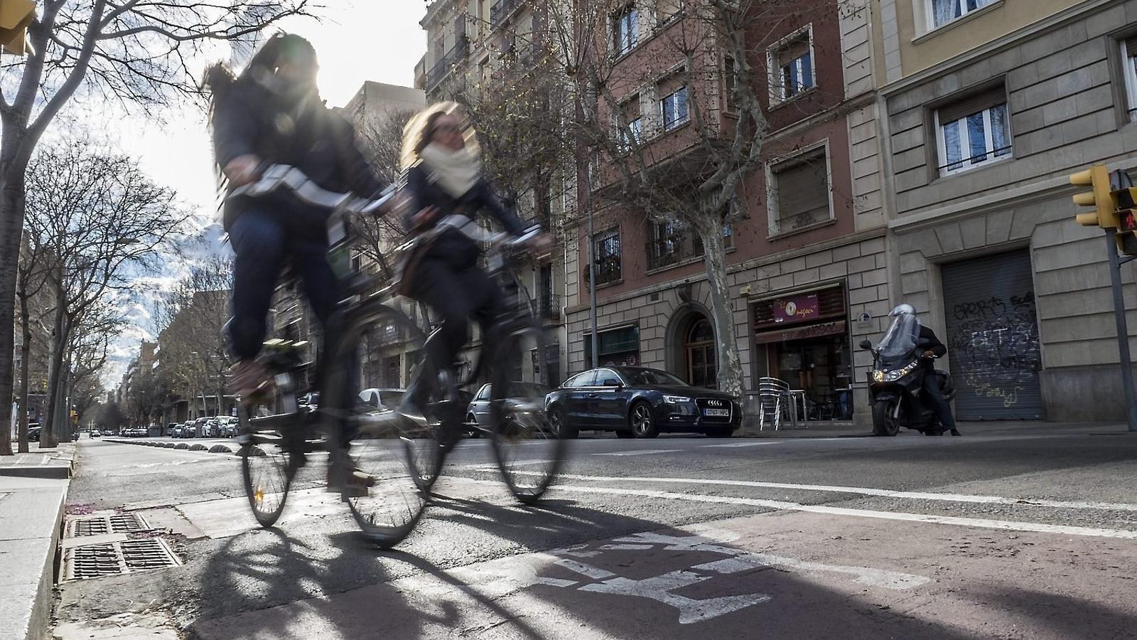 Dues noies en bicicleta pel carrer Consell de Cent