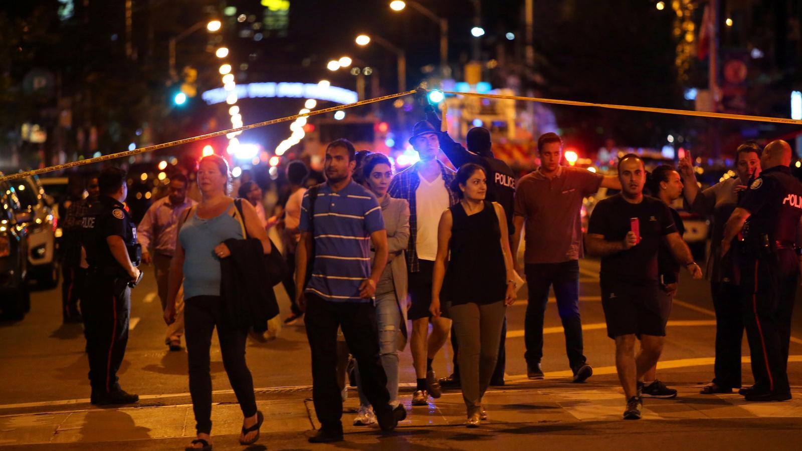 Un grup de gent desallotjada per la policia de la zona del tiroteig