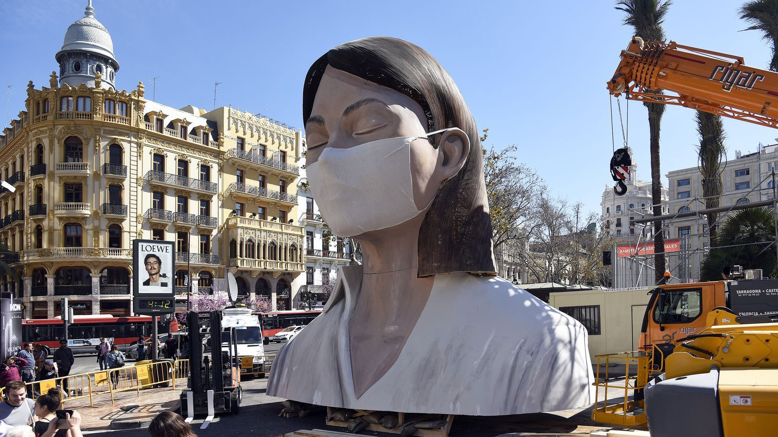 La figura principal del monument de la plaça de l'Ajuntament de València amb una màscara, després de l'ajornament inicial de les Falles a causa de l'epidèmia de coronavirus
