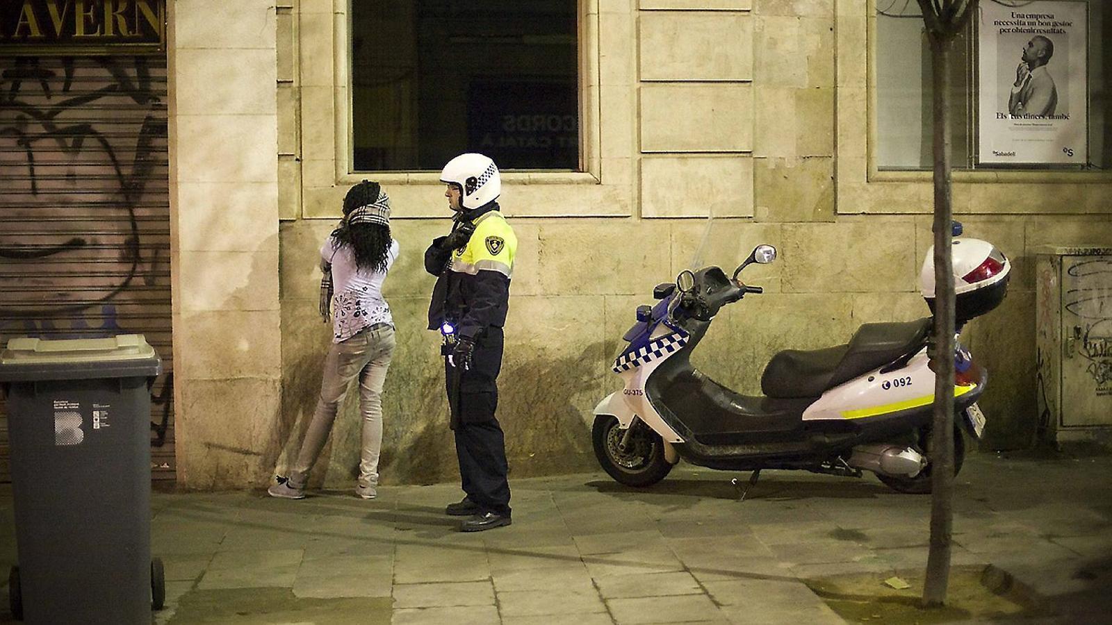 Un agent de la Guàrdia Urbana amb una dona nigeriana en una batuda contra la prostitució al Raval de Barcelona.