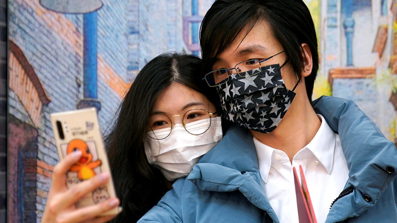 Wang, de 32 anys i la seva dona Shi, de 30 anys, amb màscares en una oficina de registre matrimonial el dia de Sant Valentí a Xangai