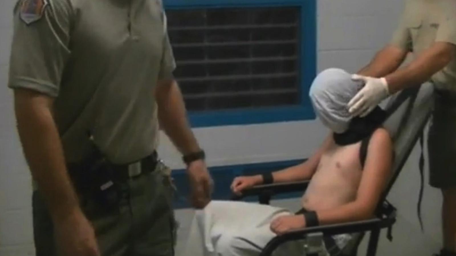 Un guàrdia tapa el cap d'un jove lligat en una cadira d'un centre de menors.