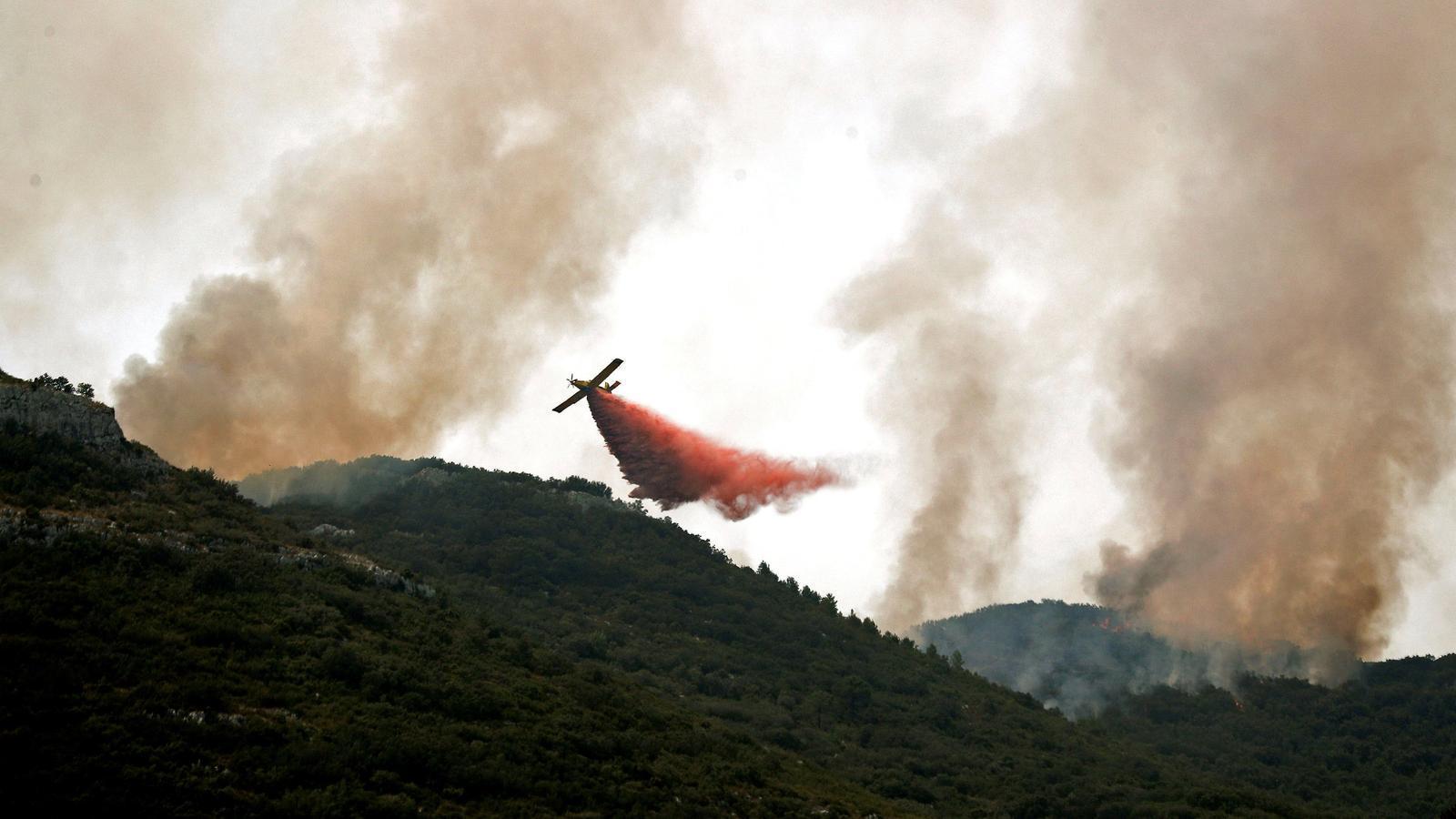 Una avioneta llança aigua amb retardants sobre el front de l'incendi de Llutxent
