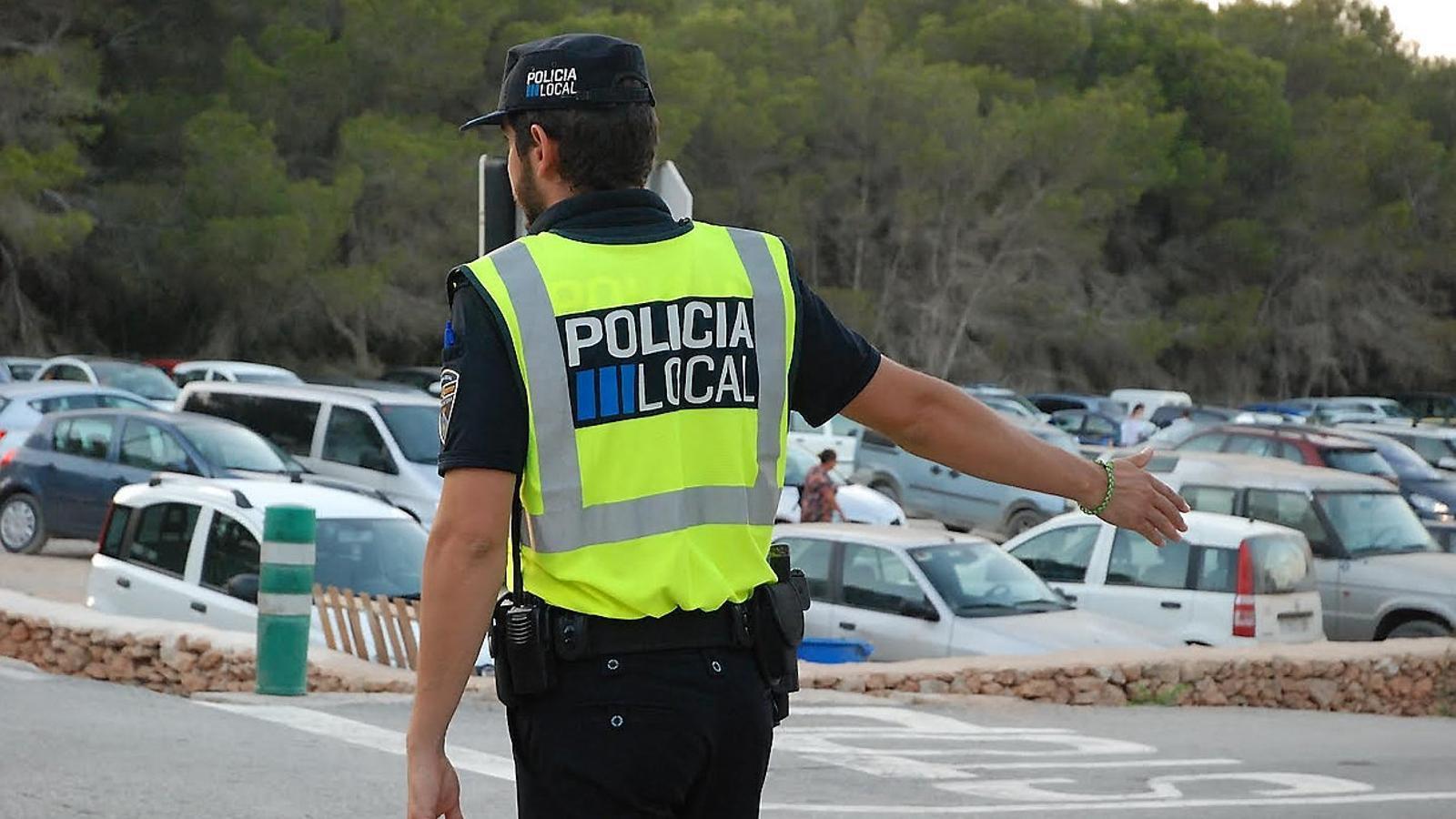 Un agent de la Policia Local dirigeix el trànsit a una zona d'aparcament.