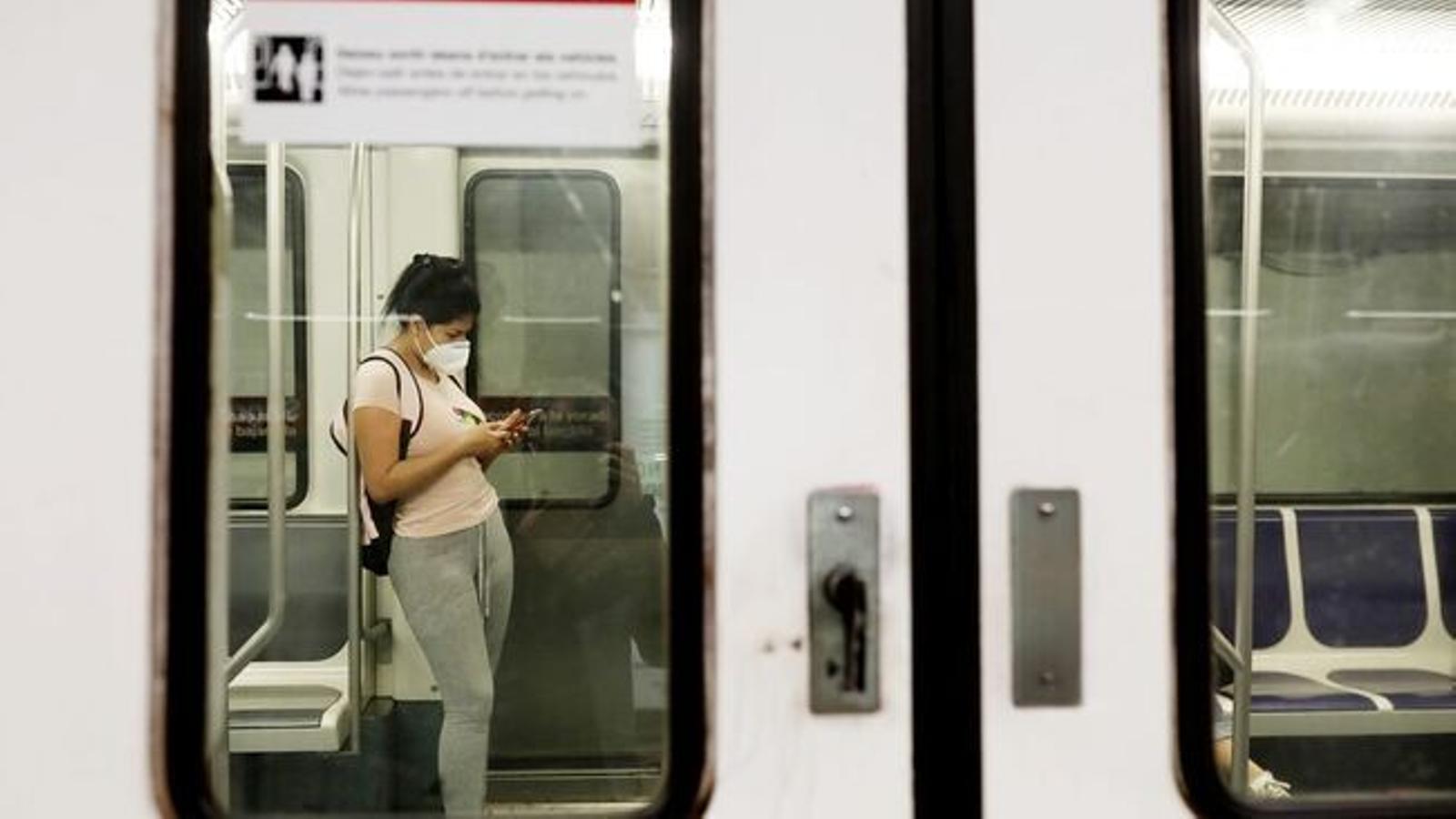 Una passatgera amb mascareta al metro de Barcelona / FRANCESC MELCION