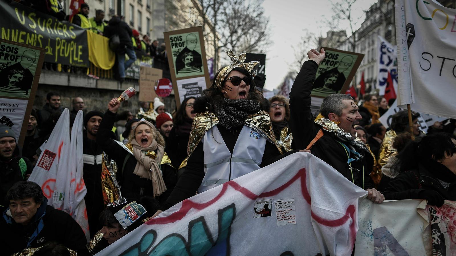 Manifestants amb mantes de supervivència criden consignes mentre participen en la manifestació contra les reformes de pensions a París