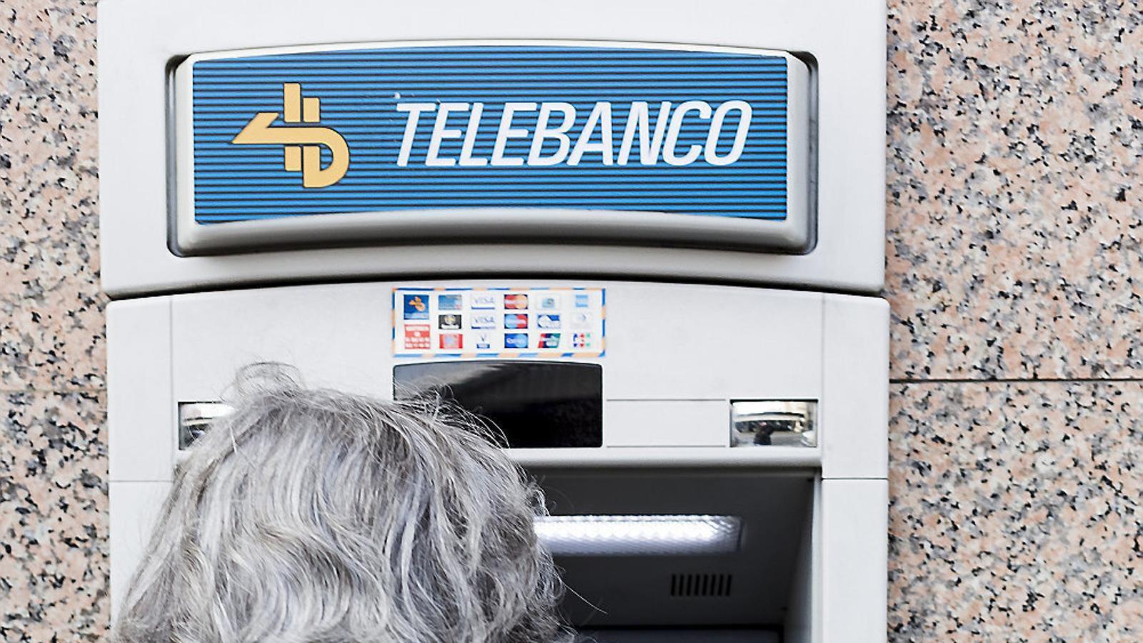 Una senyora traient diners d'un caixer automàtic.