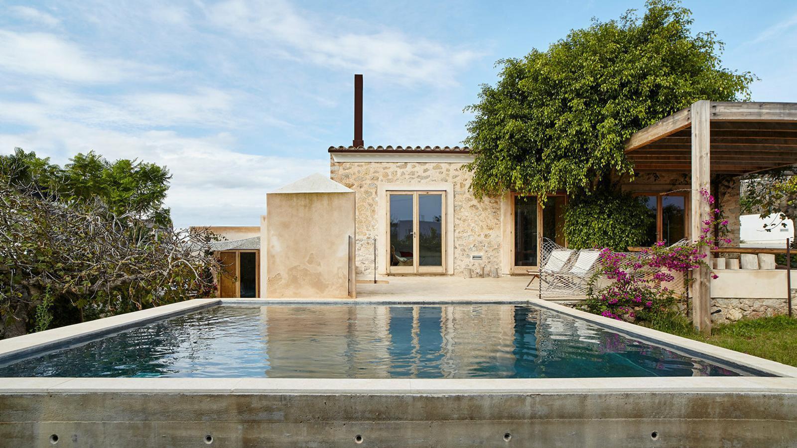 Una pèrgola de fusta ofereix un espai relaxat i ombrívol al costat de la petita piscina amb caràcter de safareig. La porxada té continuïtat amb un magatzem de fusta amb un espai per a la barbacoa.