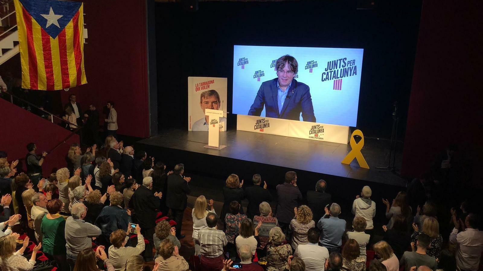El míting de Junts per Catalunya, amb la imatge del president exiliat en la pantalla