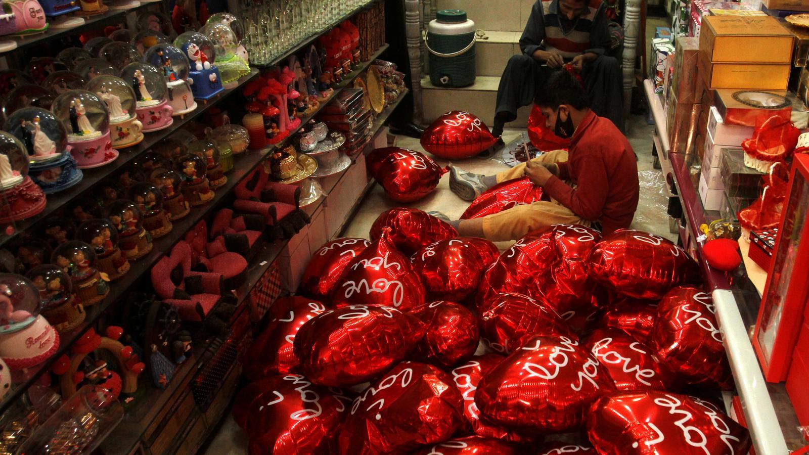 Home inflant globus en forma de cors per Sant Valentí / Fayaz Aziz