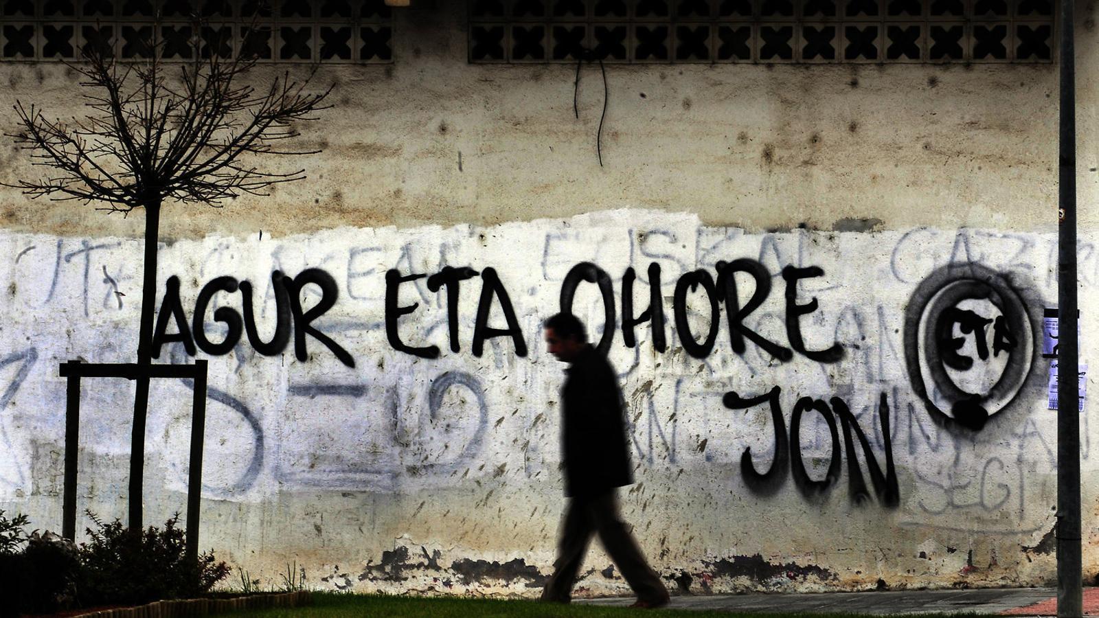 Un home caminant davant d'un mur pintat a Gernika en homenatge a Jon Antza, el cadàver del qual va ser localitzat el 2010.