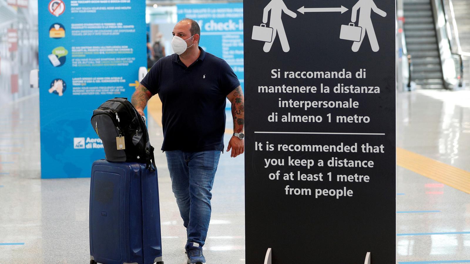Un passatger amb mascareta a l'aeroport de Fiumicino, a Roma.