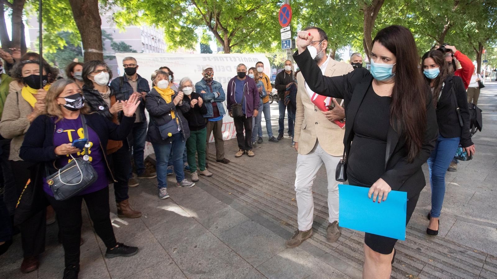 Tamara Carrasco saludant amb el puny en alt les persones que s'han concentrat a les portes de la Ciutat de la Justícia per donar-li suport el dia del seu judici