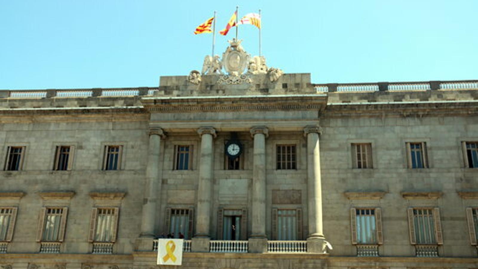 Operaris de l'Ajuntament de Barcelona col·loquen el llaç groc després de la decisió presa a la primera reunió de grups municipals