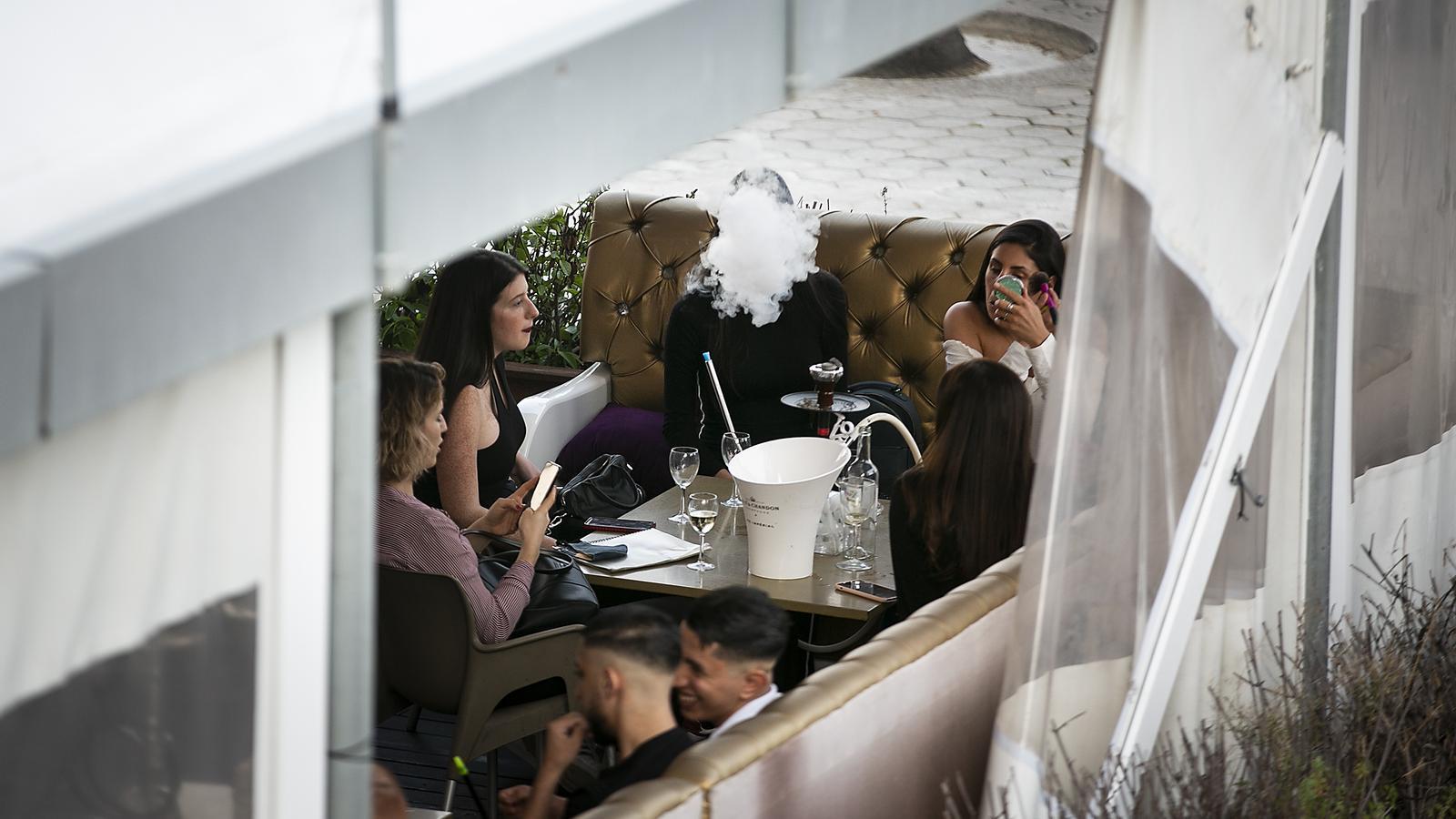 Un  grup de persones en una terrassa del Port Olímpic aquest dijous