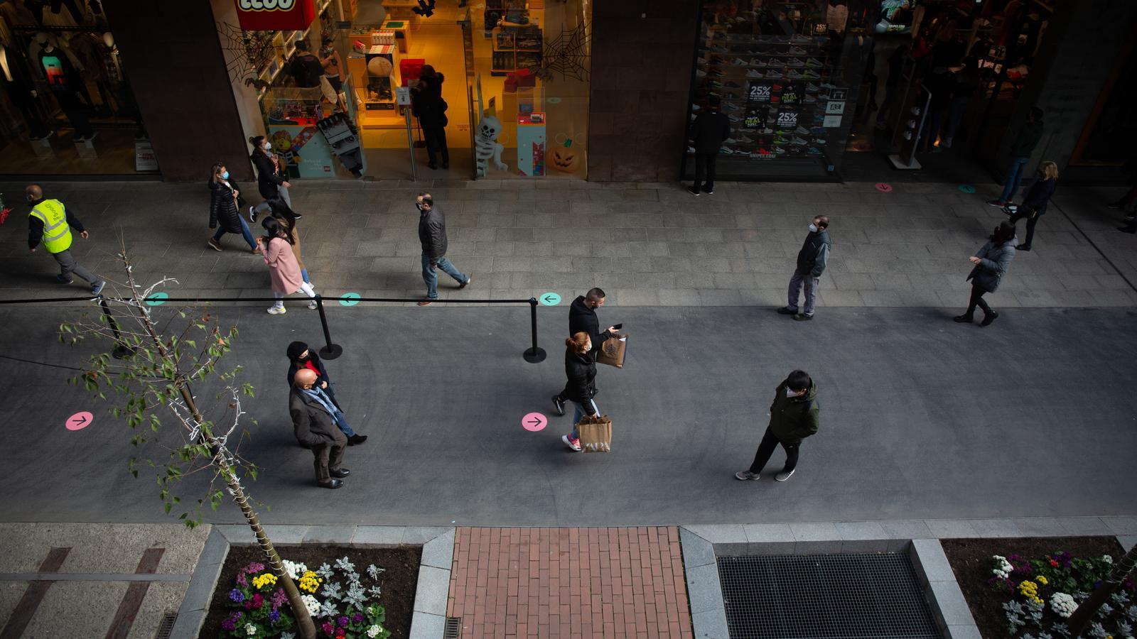 Ciutadans passejant per una zona comercial
