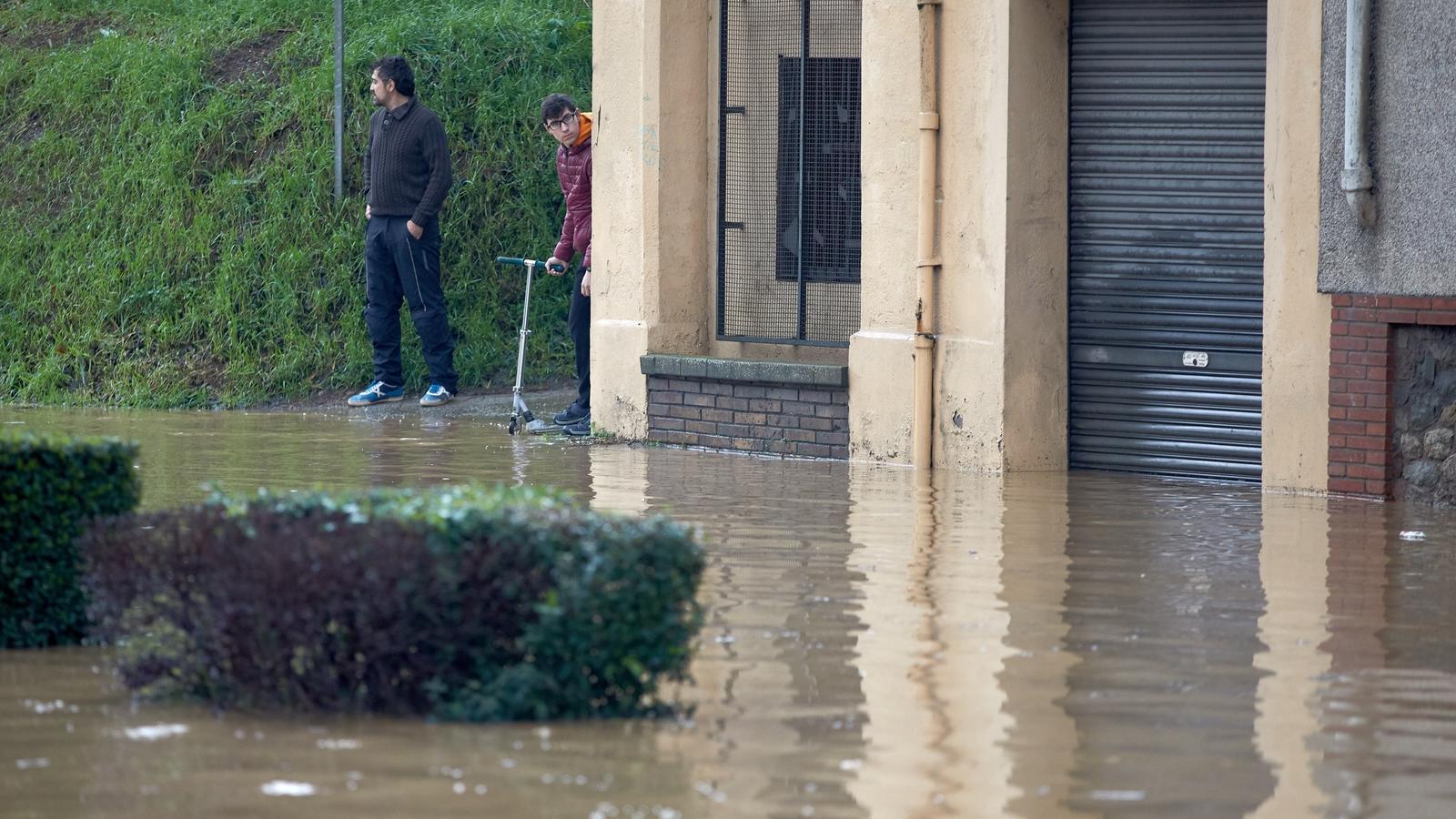 Veïns observant, dimecres, com es desborda el riu Ter al seu pas per Girona.
