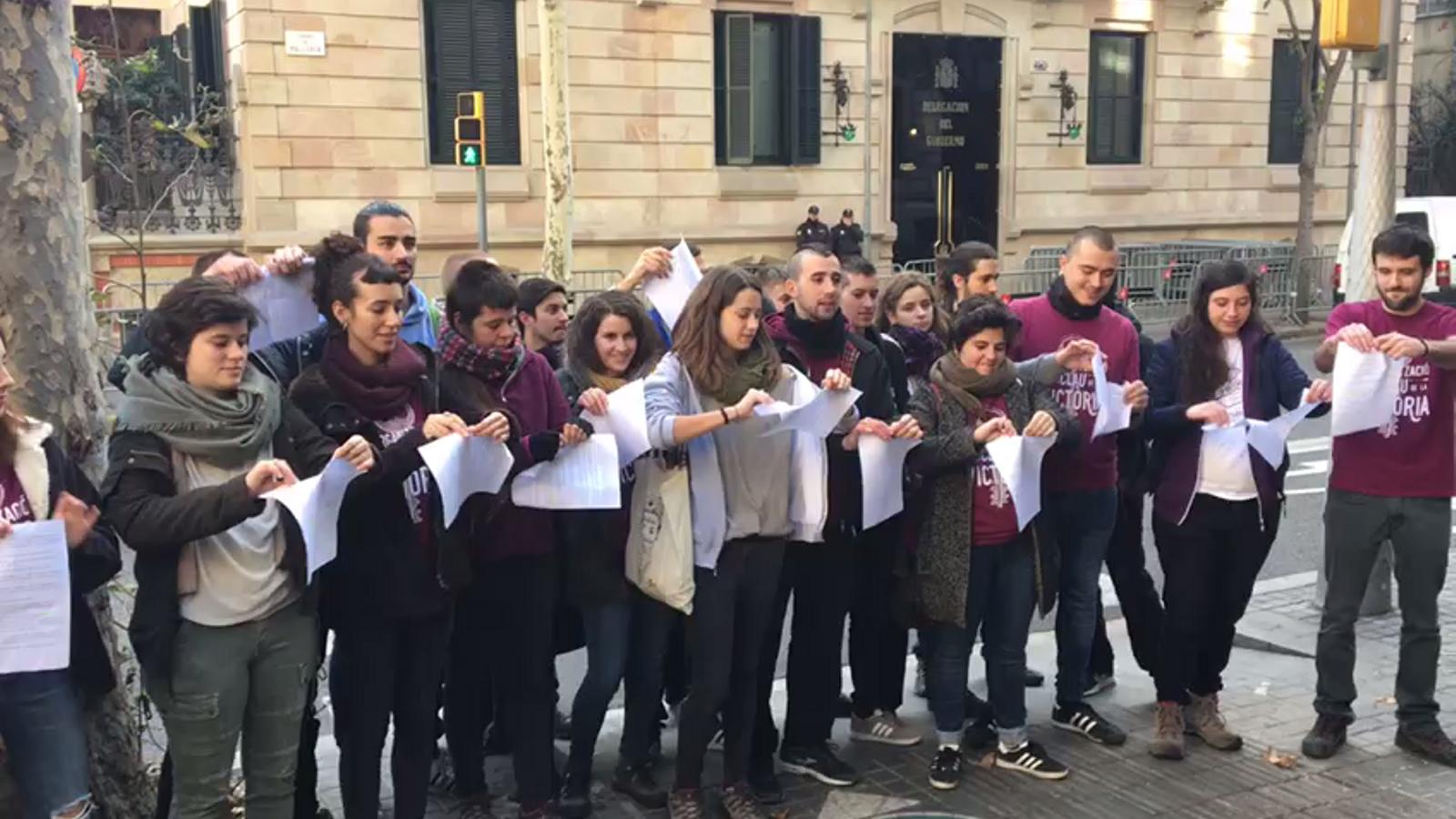 Membres d'Arran estripen l'escrit d'acusació del PP contra membres de l'organització juvenil davant la delegació del govern espanyol.