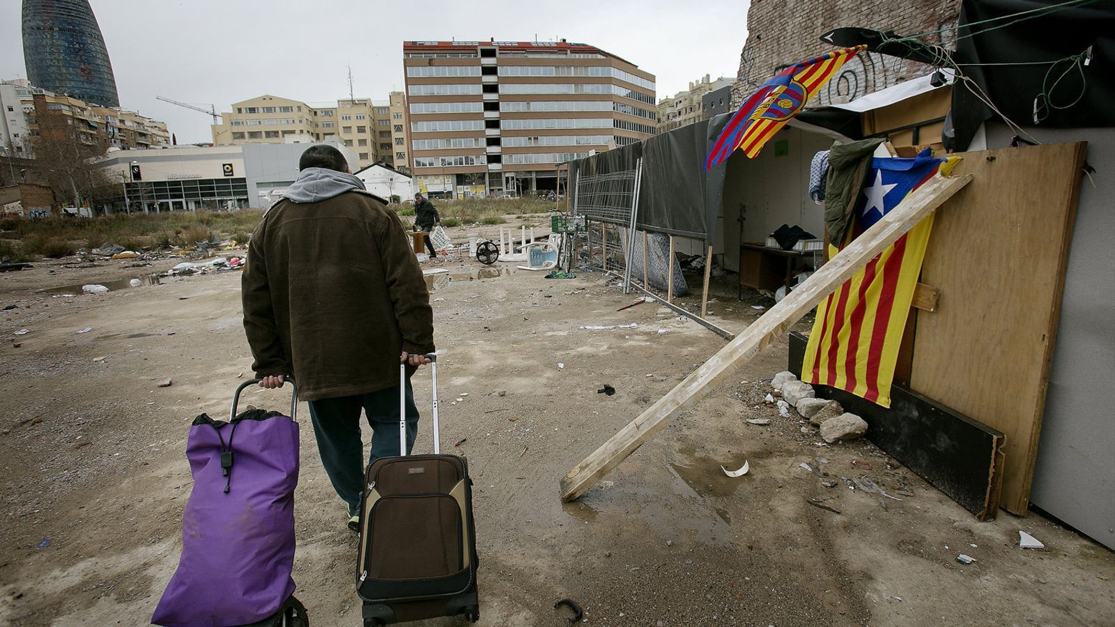 El Doro, un home romanès, arribant carregat de maletes a la seva barraca, en un solar situat al costat de la plaça de les Glòries.