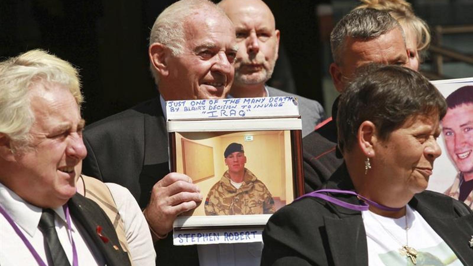 Familiars dels soldats britànics morts a l'Iraq mostren fotografies de les víctimes a les poetes on Chilcot ha presentat el seu informe. / SEAN DEMPSEY / EFE