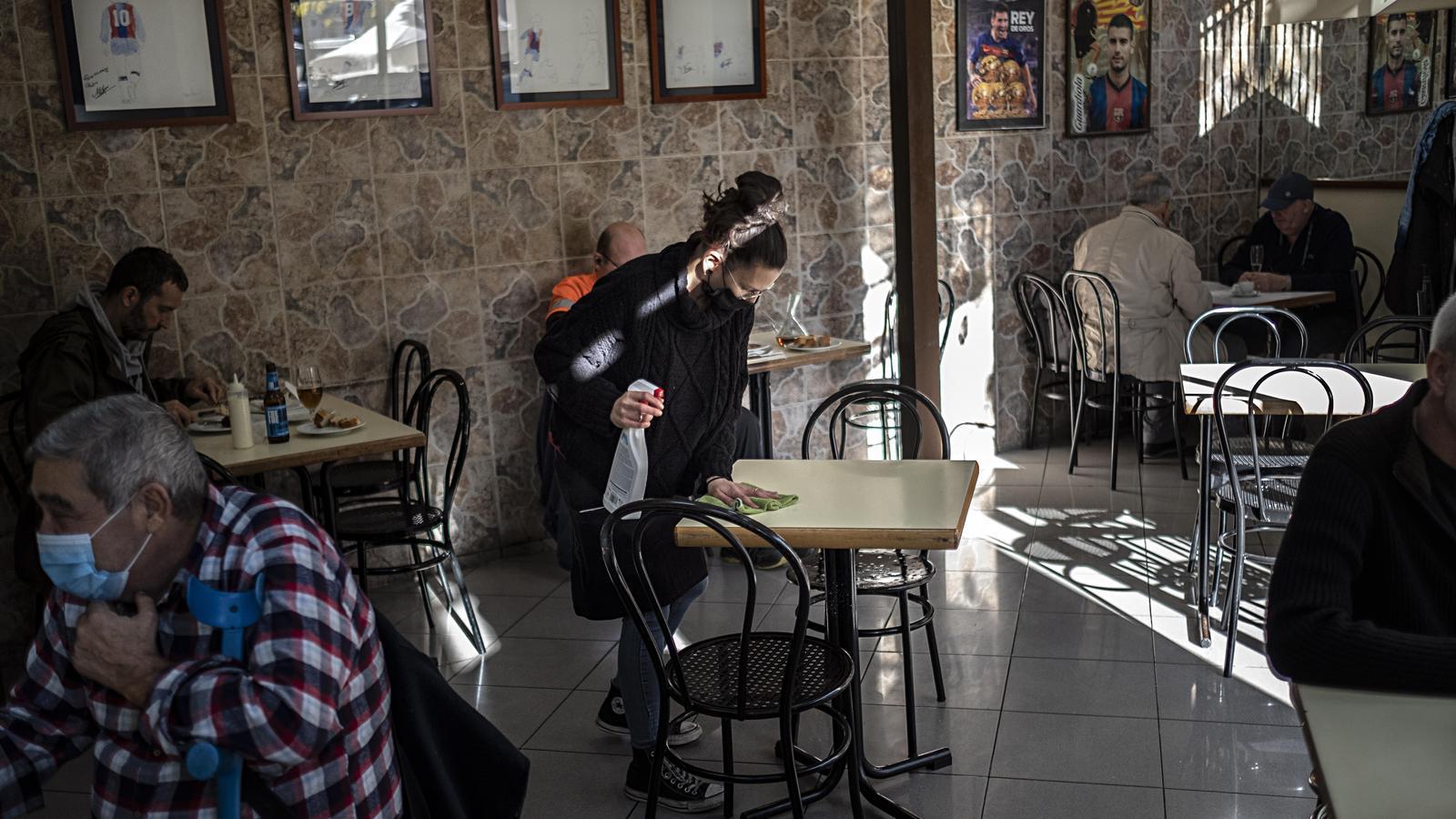 Una cambrera netejant una taula en un restaurant de l'Eixample de Bacelona amb l'aforament reduït