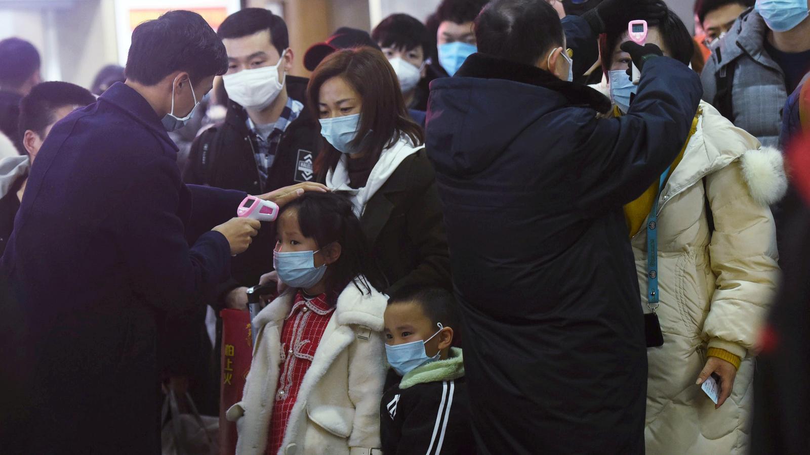 Personal de l'estació de tren de Hangzhou pren la temperatura a passatgers que provenen de Wuhan, una de les ciutats aïllades