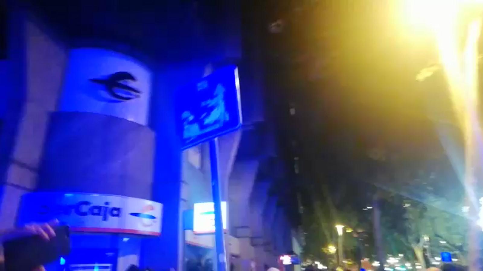 Un manifestant llança una senyal de trànsit davant la delegació del govern espanyol
