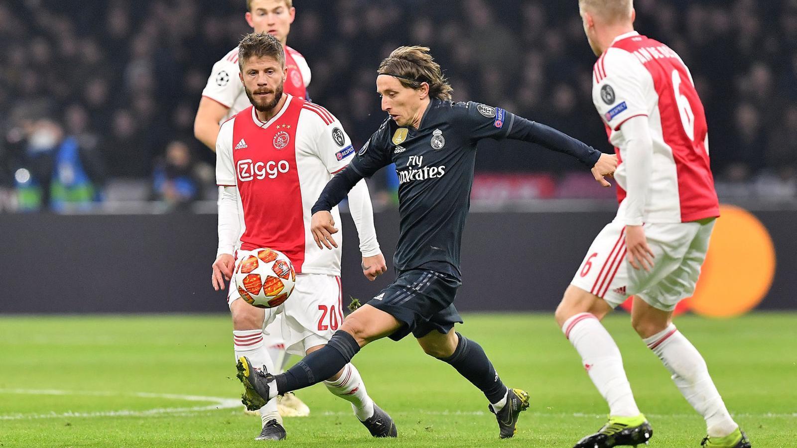 Luka Modric mirant de controlar una pilota al mig del camp entre Van de Beek i Schöne. El Madrid va patir per connectar amb el croat.