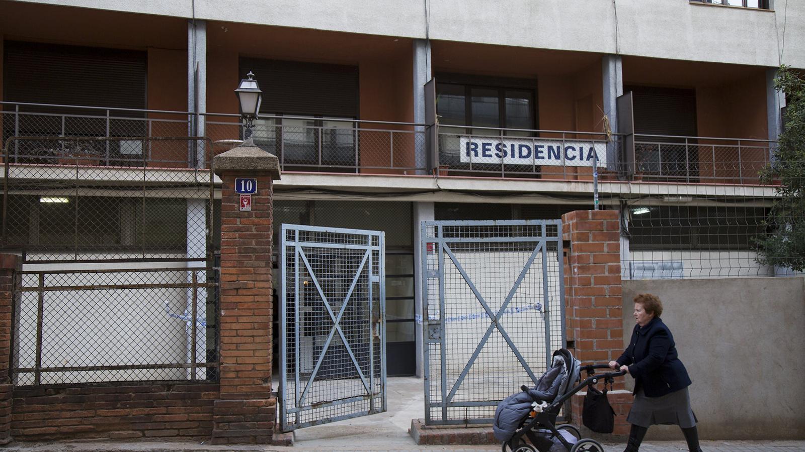 Un dona passant amb un cotxet per davant d'una residència de gent gran a Barcelona.