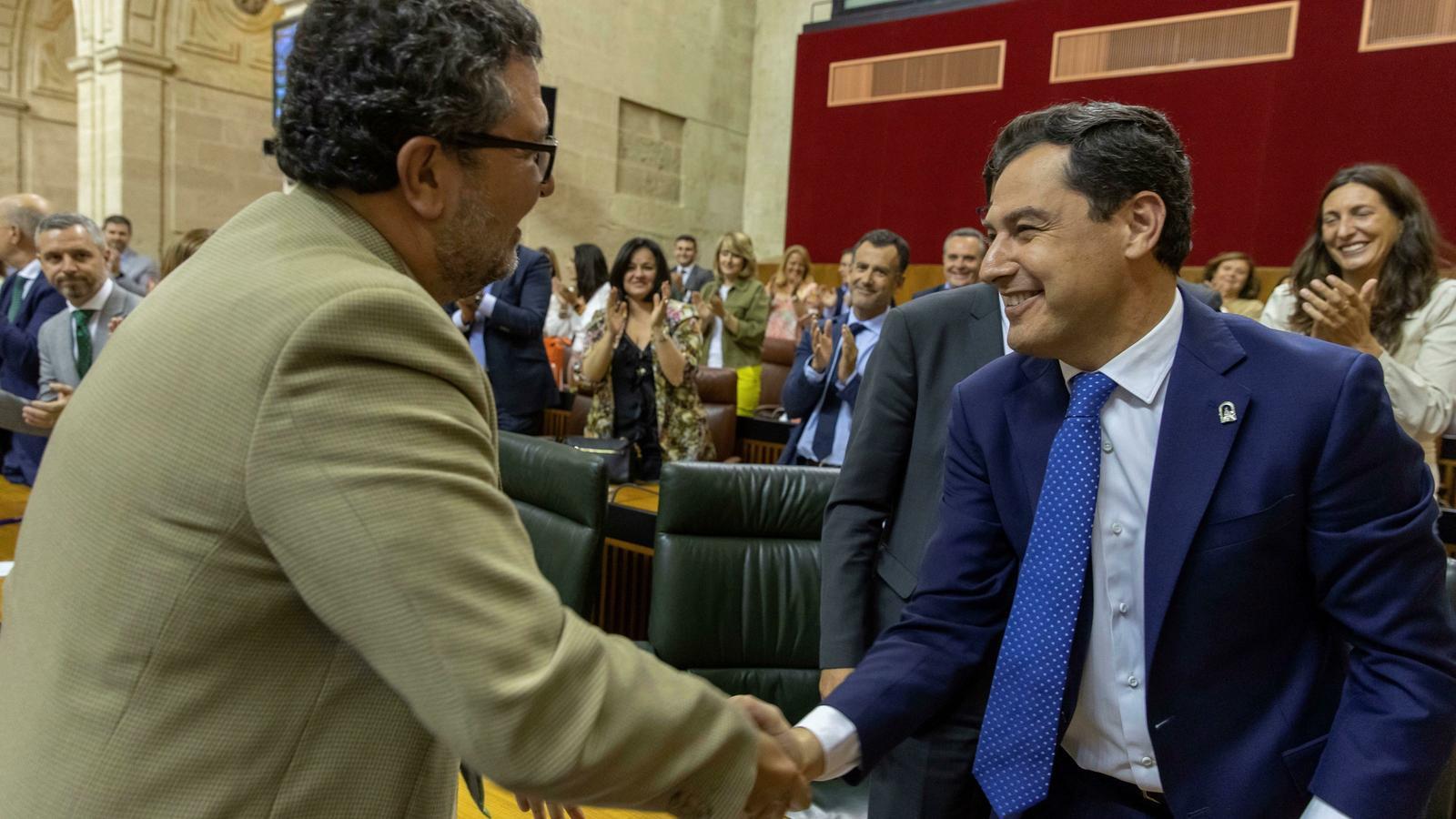 El president andalús, Juanma Moreno, i el president del grup parlamentari de Vox, Francisco Serrano, es donen la mà simbolitzant el pacte