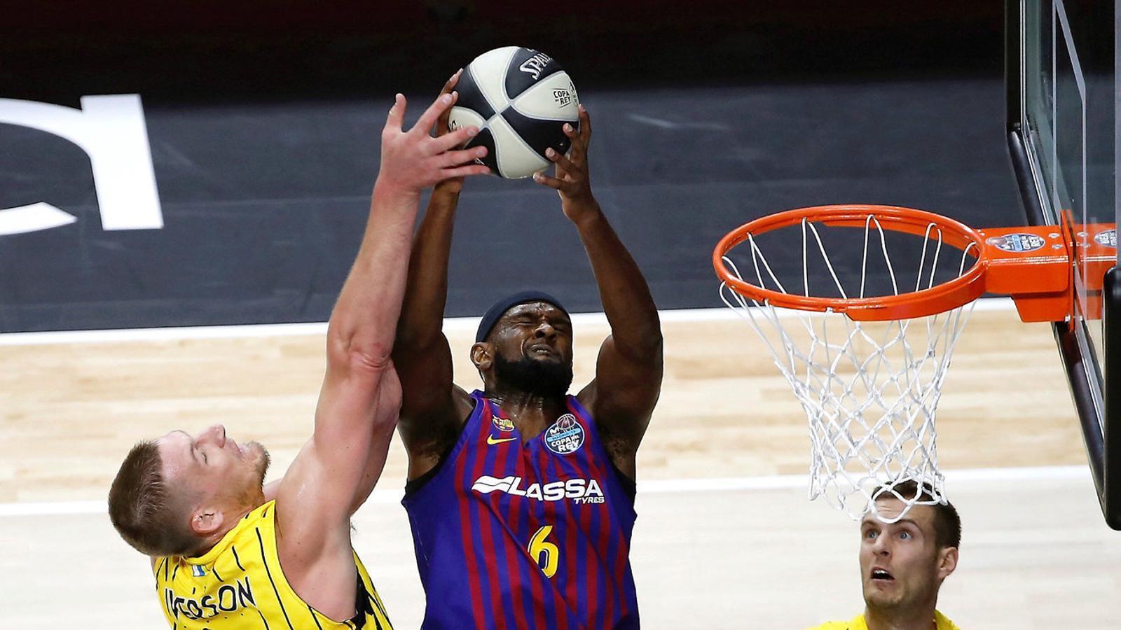 Chris Singleton, aler pivot del Barça Lassa, intentant allunyar la pilota de Colton Iverson, jugador de l'Iberostar Tenerife.