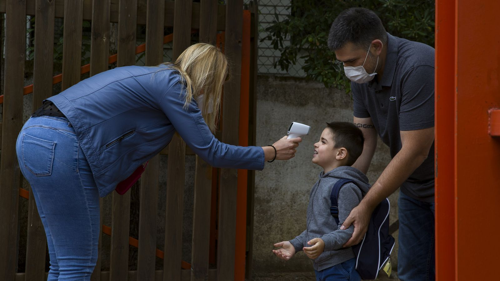 Una dona li pren la temperatura a un nen en el primer dia d'escola després del confinament pel covid-19  a l'escola Garbé d'Esplugues de Llobregat. Imatge del 8 de juny del 2020