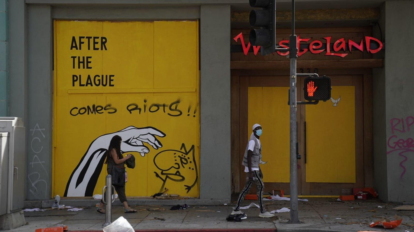 """Un cartell que diu """"Després de la plaga, arriben els disturbis"""", en un carrer de Santa Monica, a Califòrnia"""