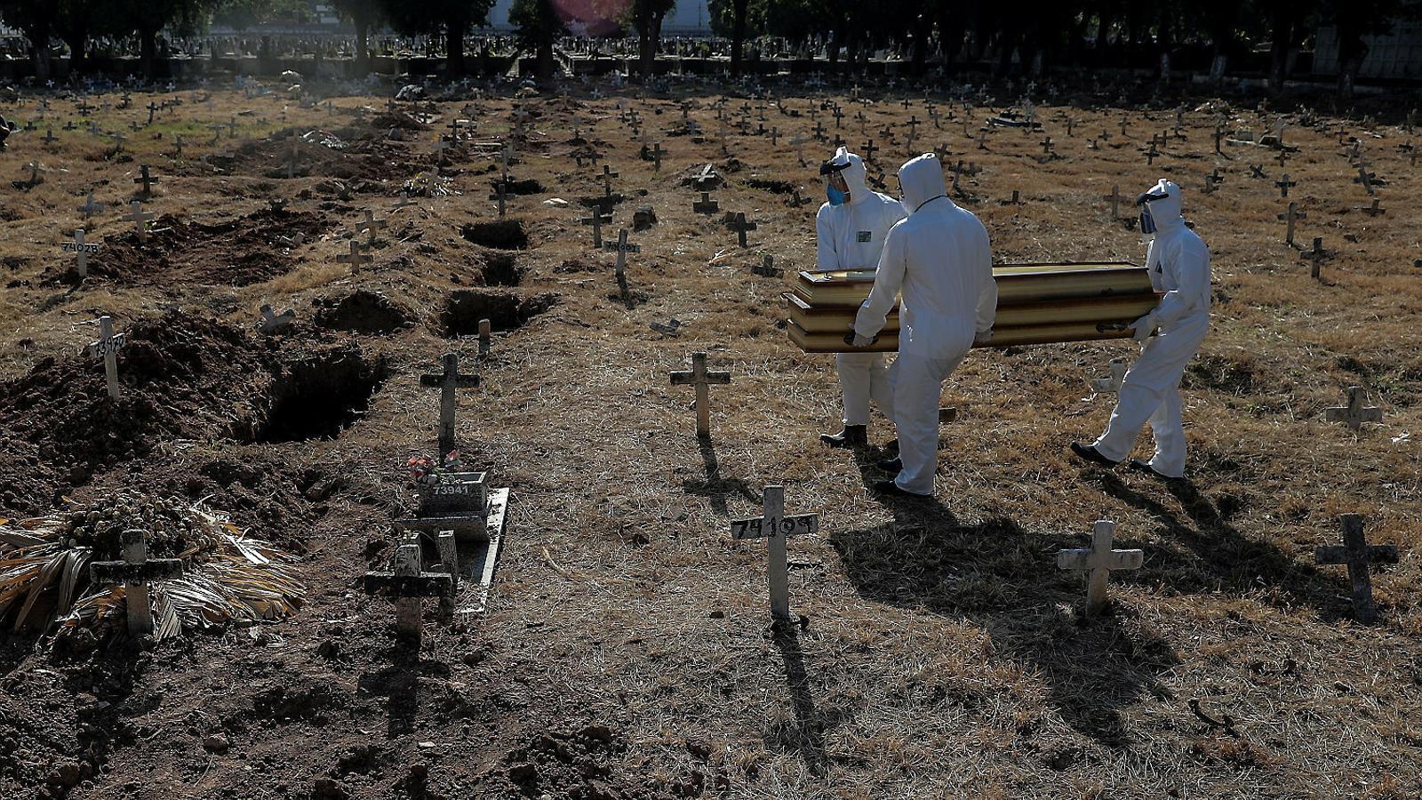 Operaris del cementiri de Cajú, a Rio de Janeiro, portant a enterrar  el taüt d'una víctima mortal del coronavirus.