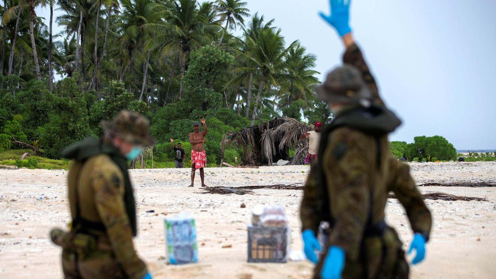 Membres dels equips de rescat saluden els tres homes que esperaven ser rescatats en una illa deserta del Pacífic.