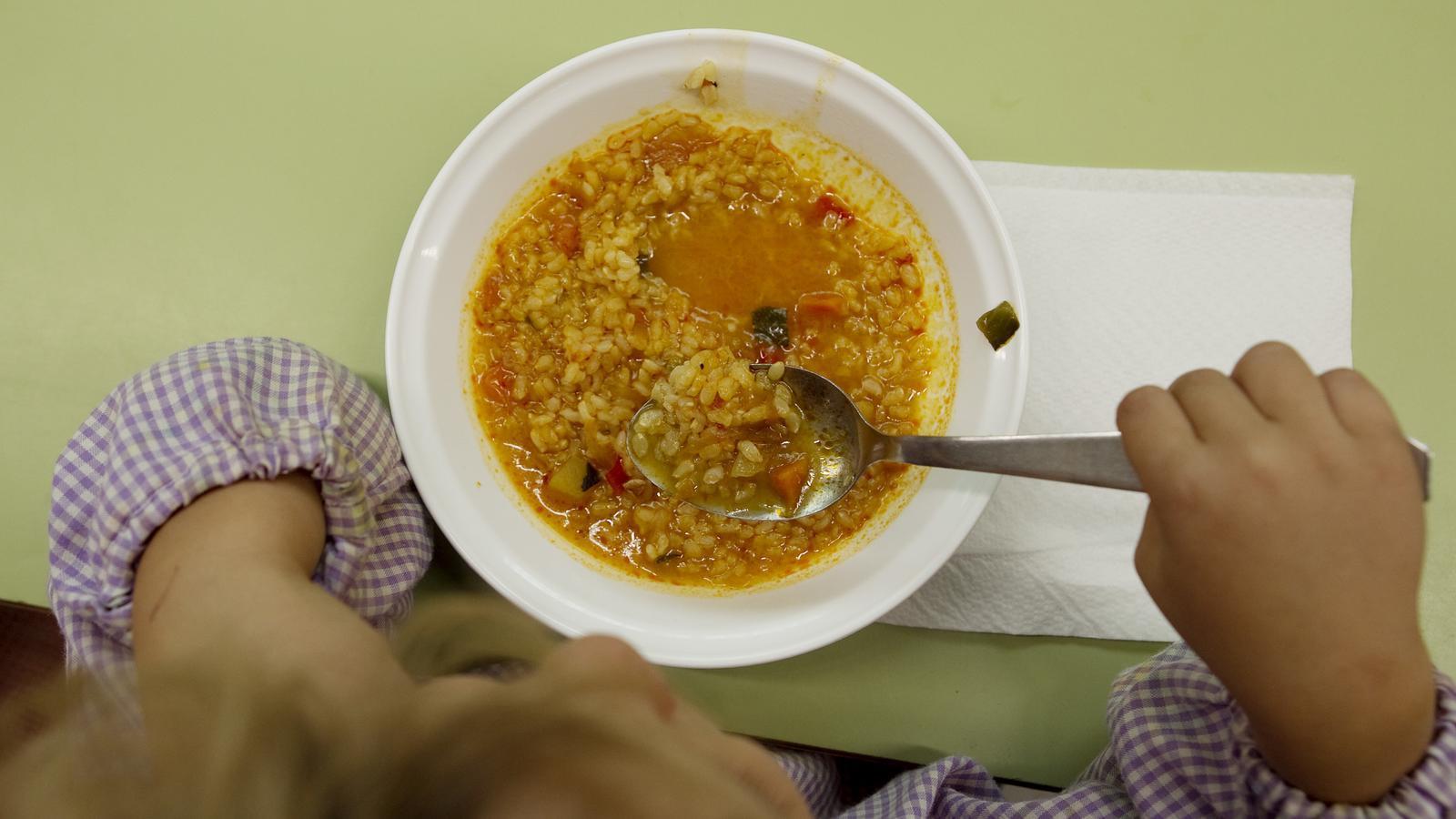 Un infant al menjador escolar.