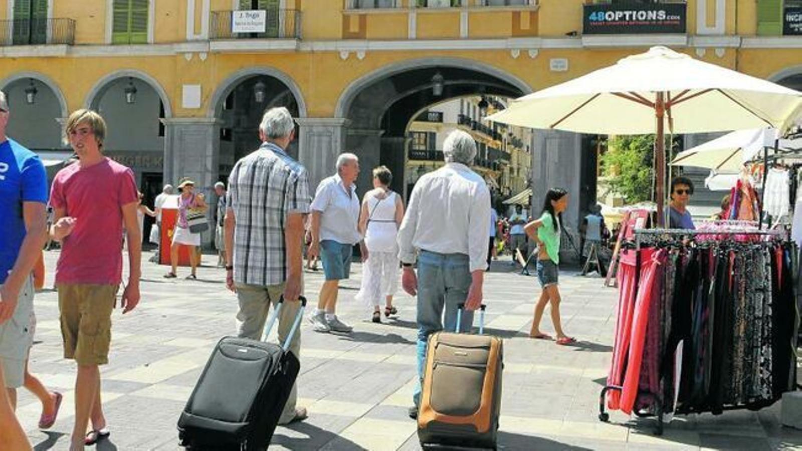 Turistes amb les seves maletes per la plaça Major de Palma.