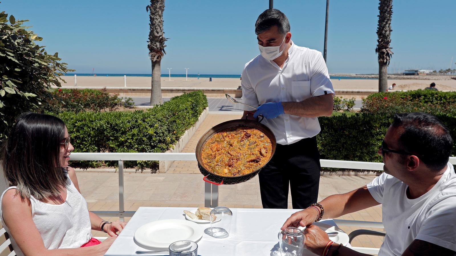 Un cambrer serveix una paella en una terrassa d'un restaurant de la platja de la Malvarrosa de València