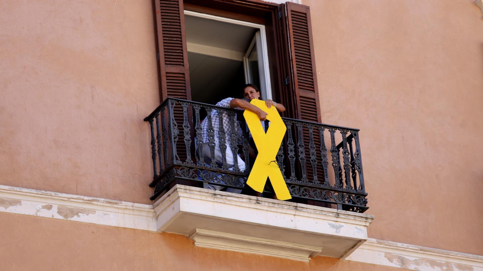 Moment de la retirada del llaç groc dels exteriors de les oficines de MÉS per Mallorca en el Parlament