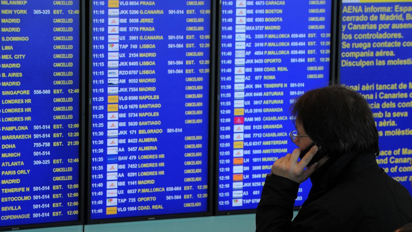 Un passatger davant la pantalla que anuncia els vols suspesos i les possibles sortides. Foto: AFP.
