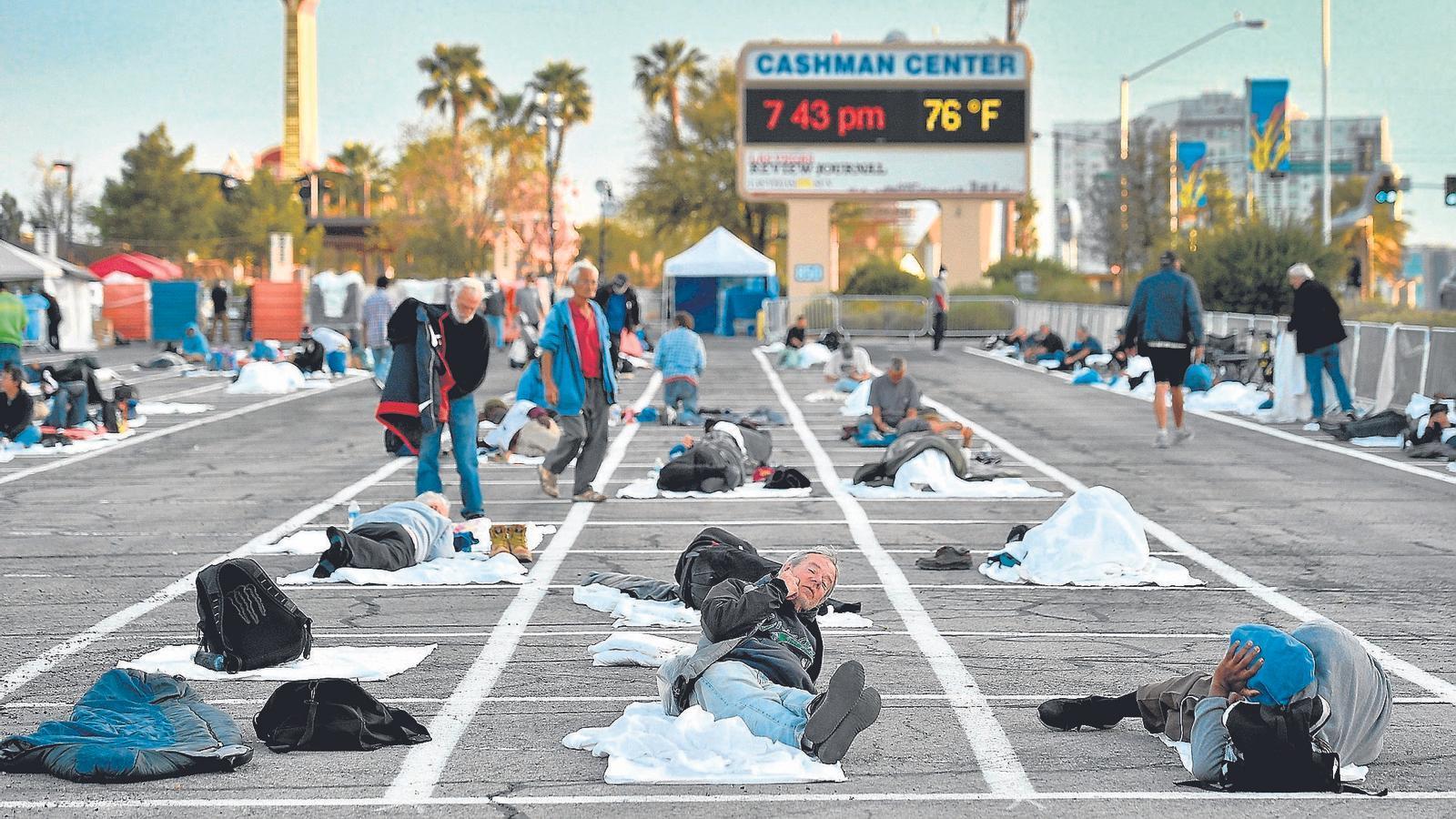Desenes de persones sense llar es preparen per dormir en l'aparcament que Las Vegas ha reservat per a ells, marcat amb línies perquè mantinguin  la distància