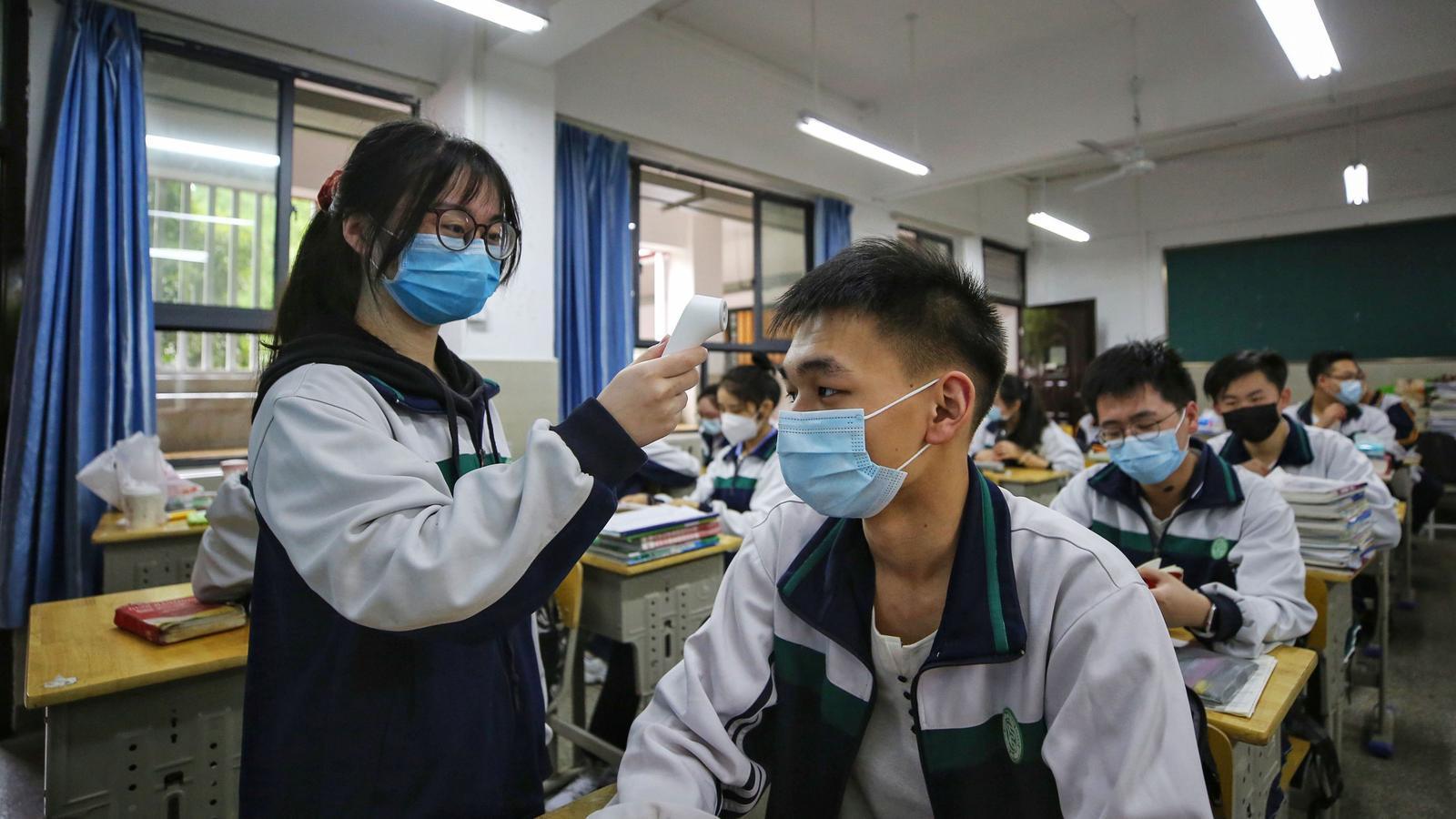 Una alumna prenent la temperatura a un company en el primer dia de classe a Wuhan després del confinament pel coronavirus
