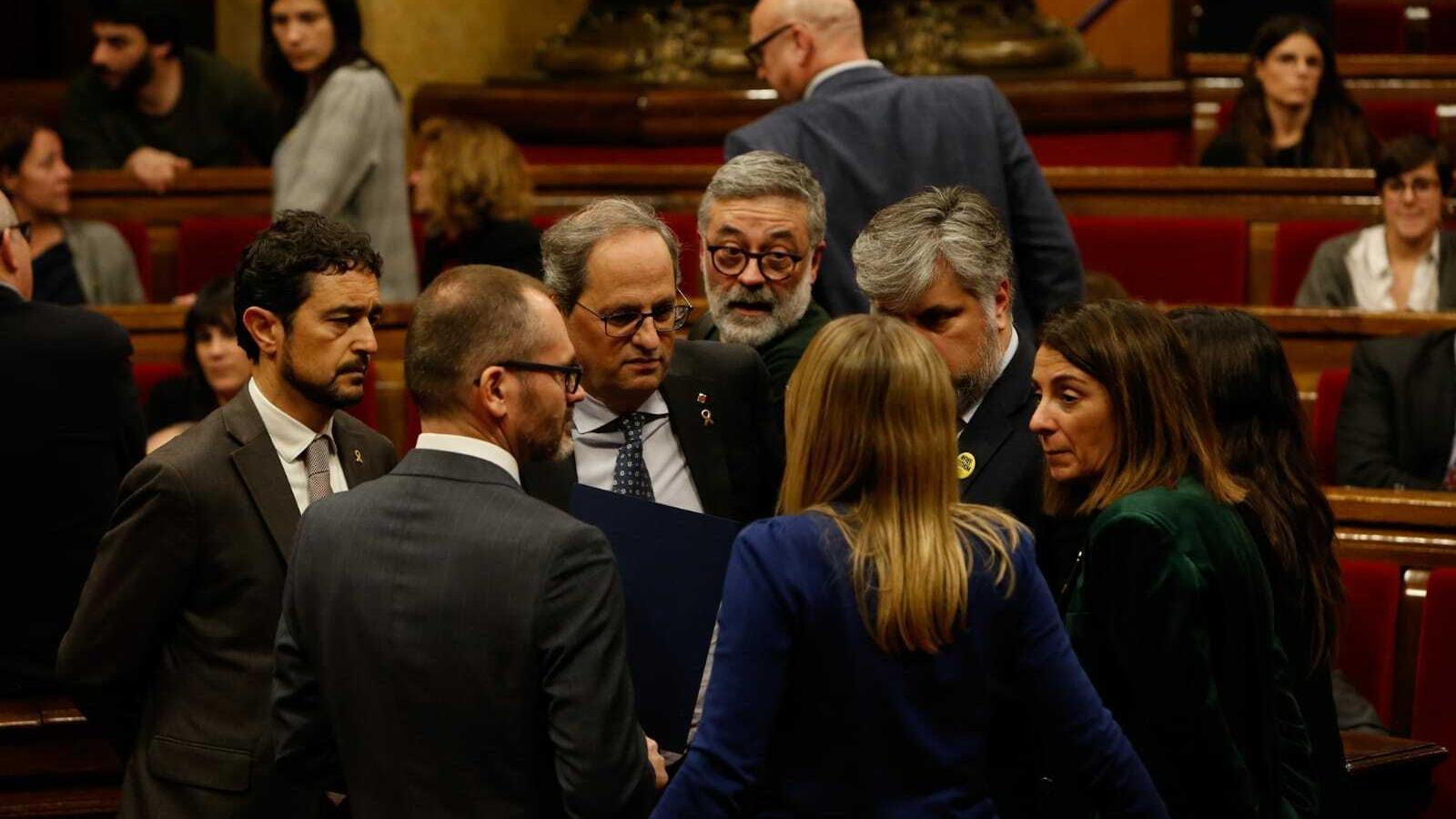 Torra conversa amb alguns diputats de JxCat en un dels recessos del ple d'aquest dilluns. Just darrere de Torra, hi ha el diputat de la CUP Carles Riera