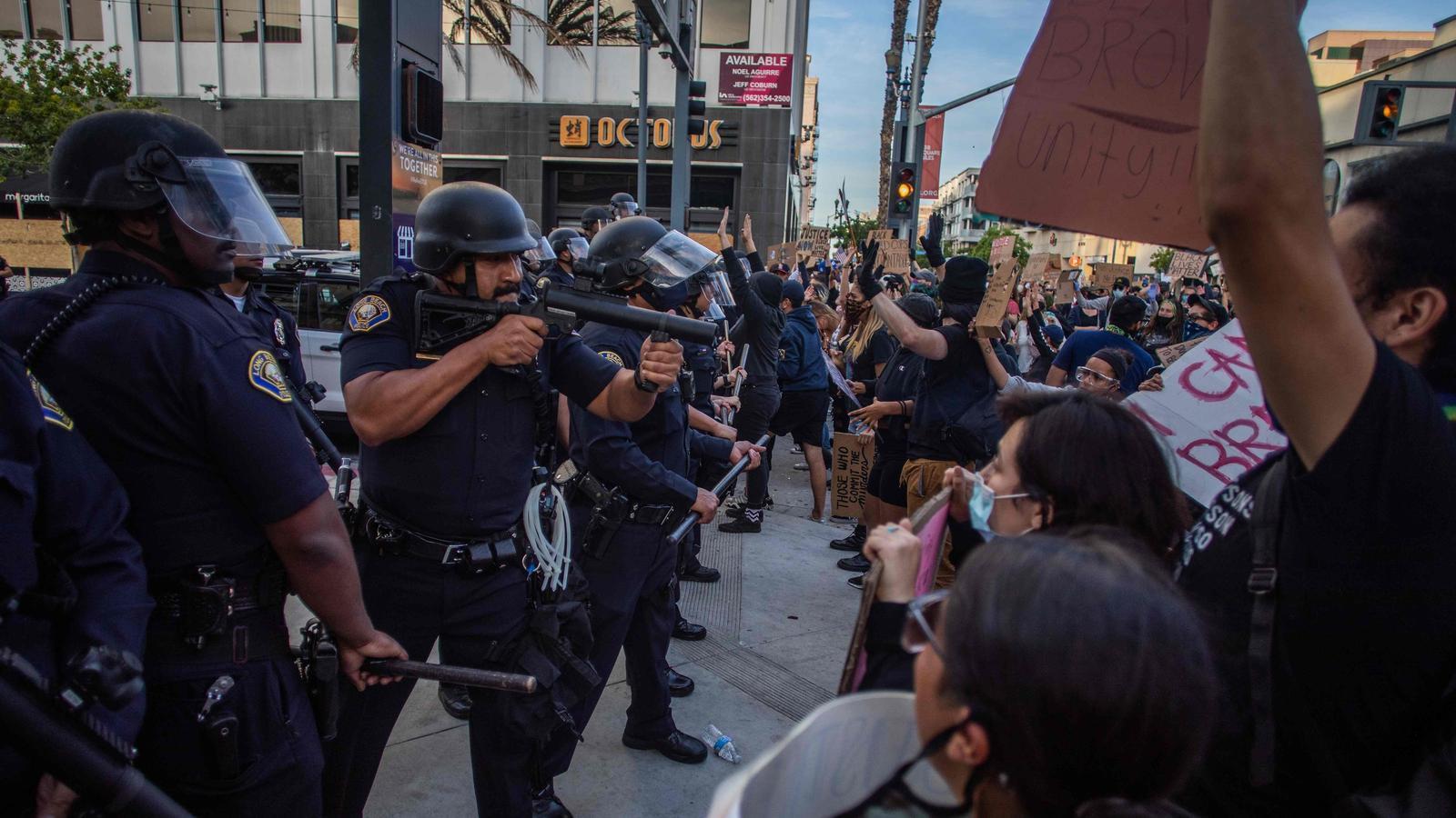 Un policia apuntant amb la seva pistola de bales de goma els manifestants que protesten a Long Beach, Califòrnia
