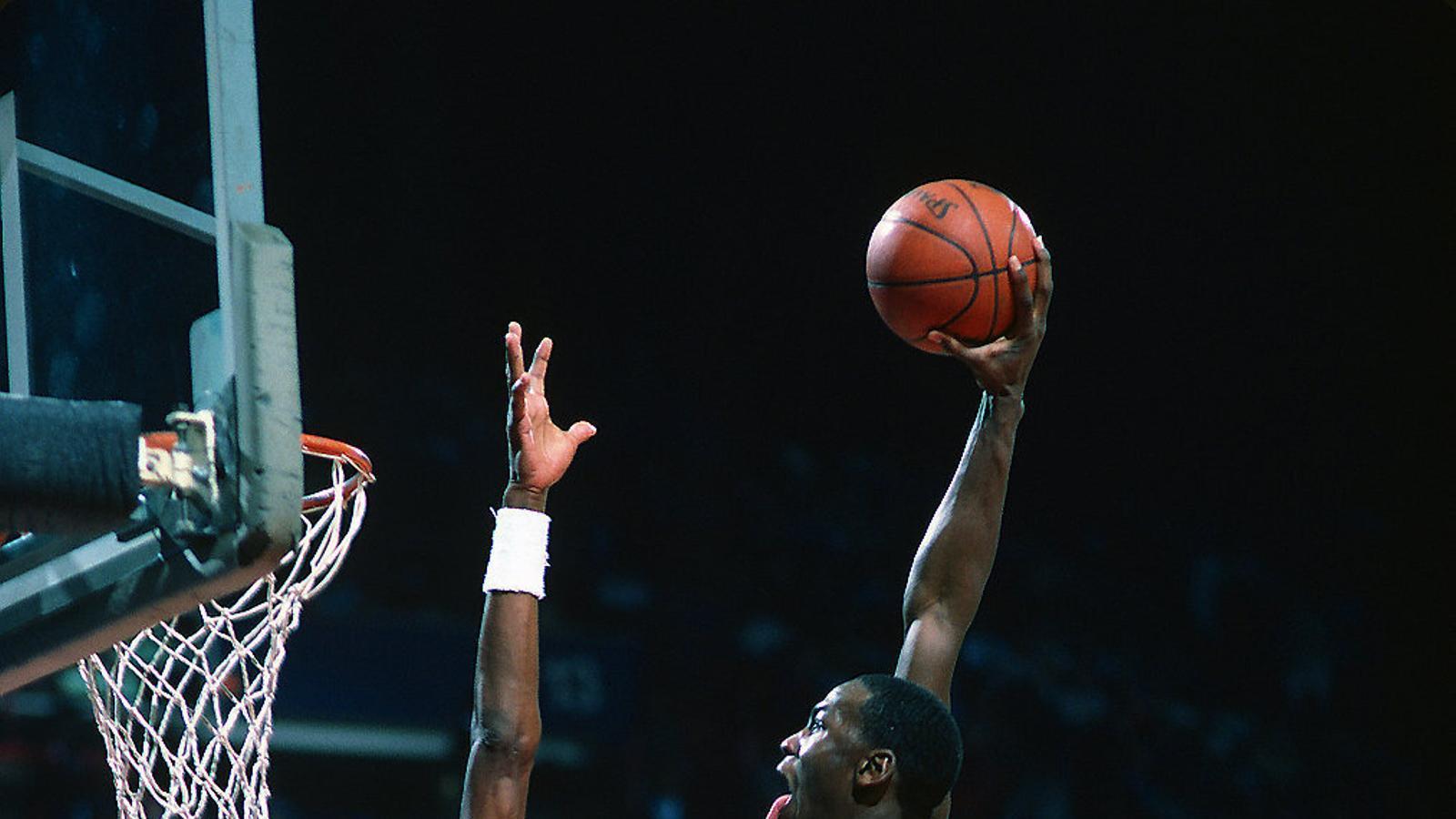 Michael Jordan intenta fer una esmaixada davant del jugador Charles Jones dels Washington Bullets en un partit de la NBA del 1985.