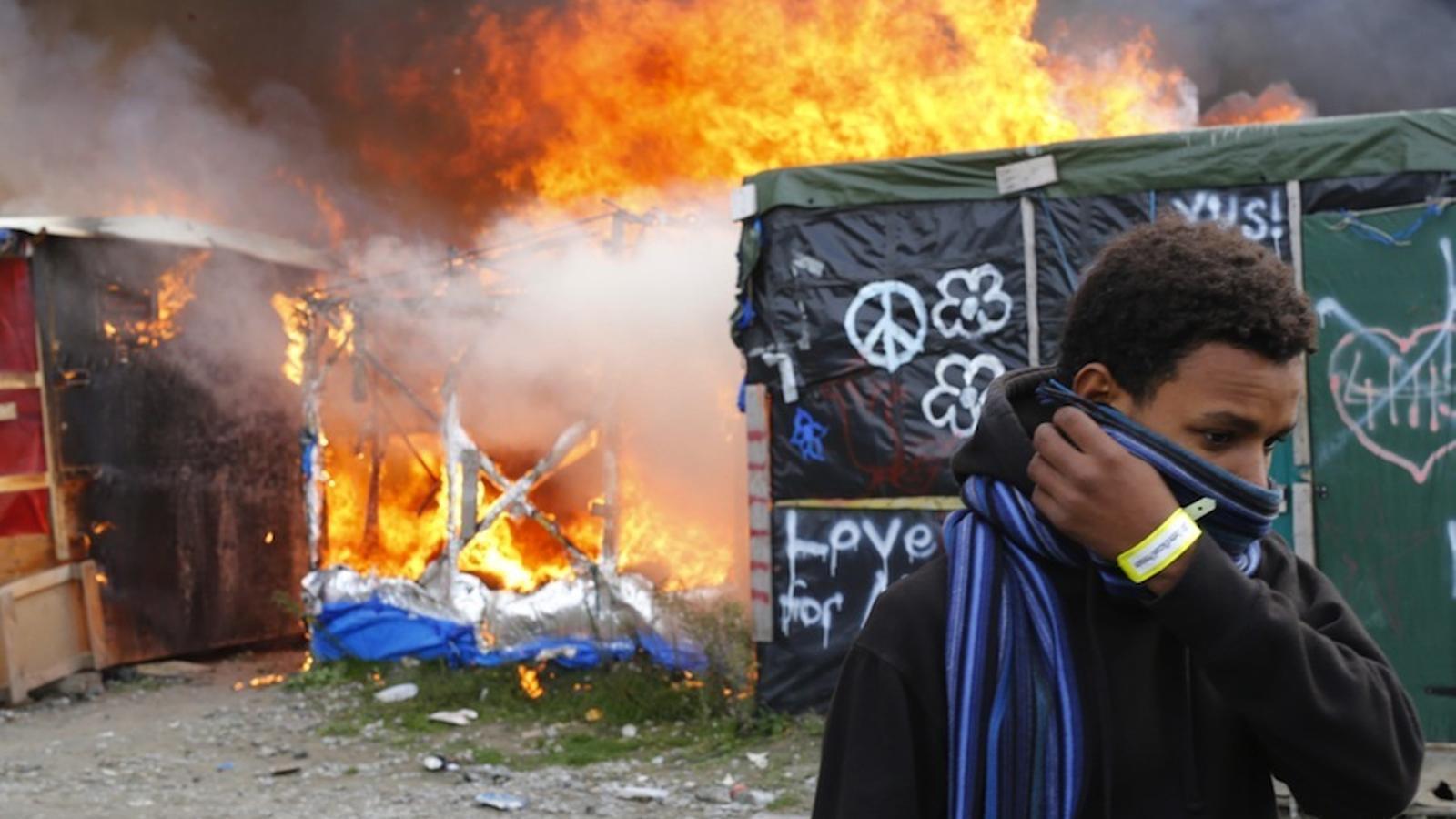 """Un migrant es protegeix la cara en passar al costat de barraques en flames durant el desmantellament del campament conegut com """"La Jungla"""" de Calais"""