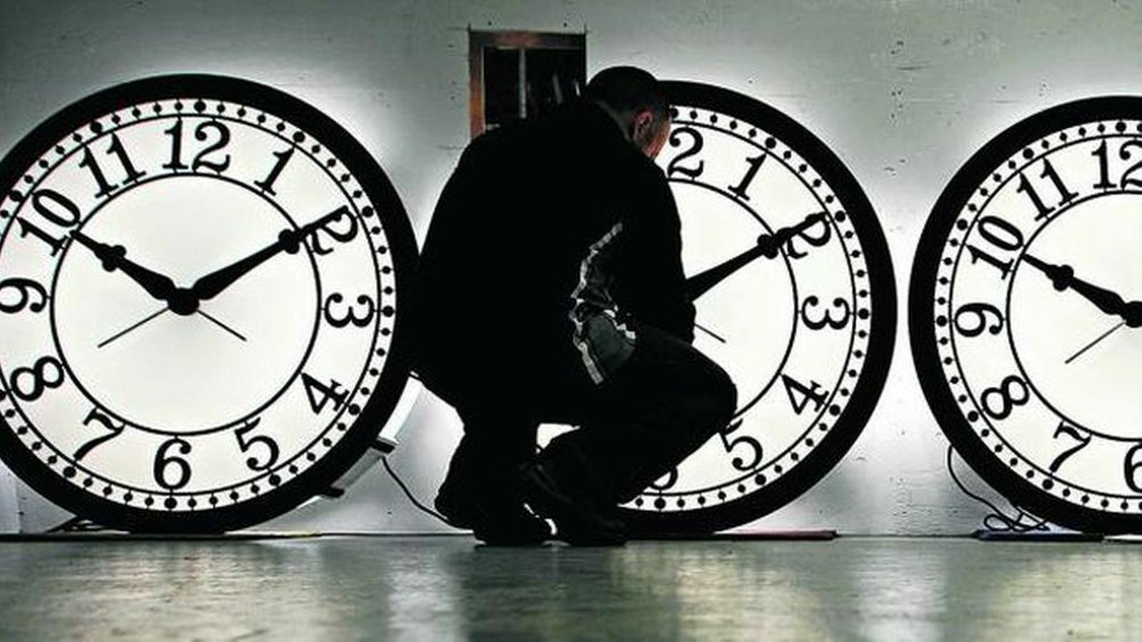 Imatge d'arxiu d'un operari canviant l'hora a uns rellotges.