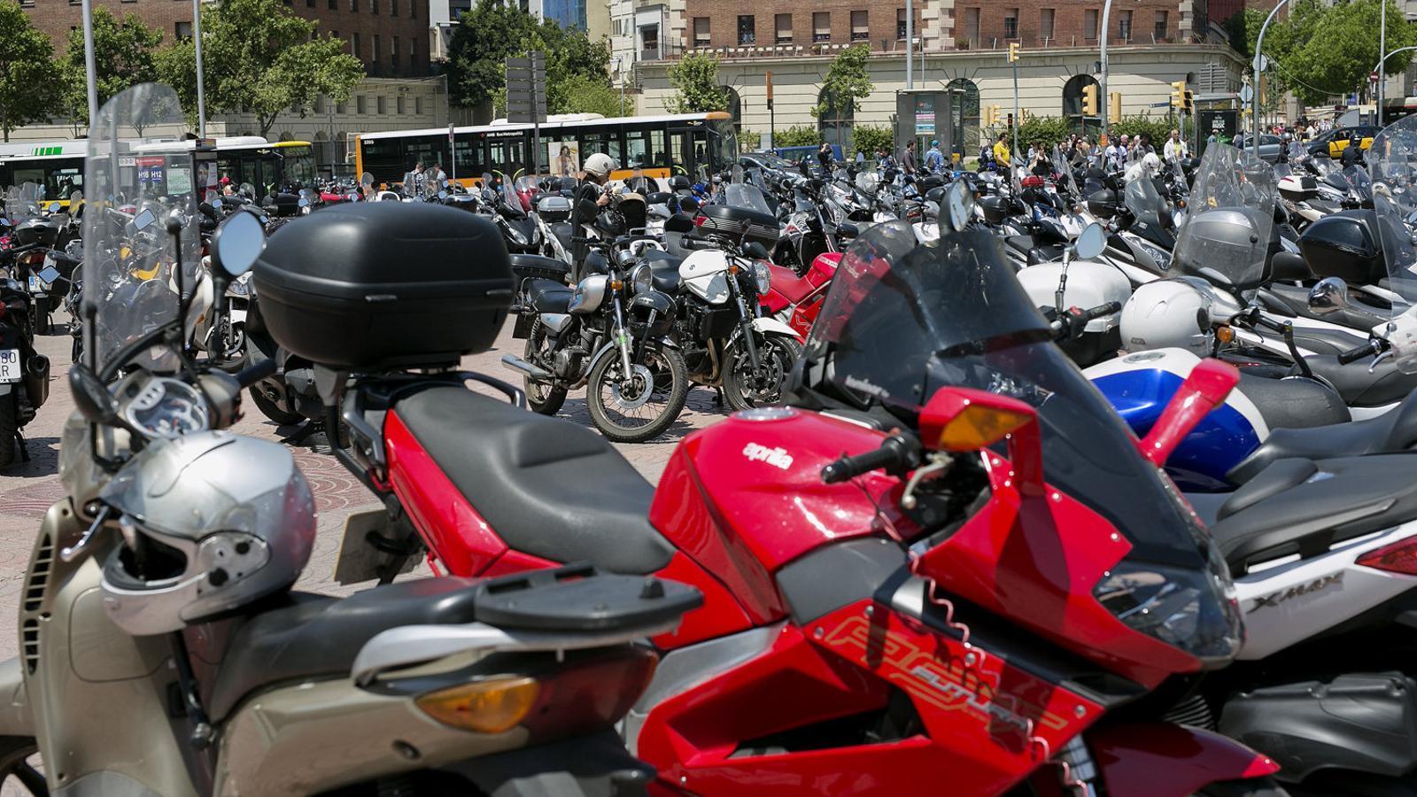 Un grapat de motos aparcades sobre una vorera de la plaça d'Espanya de Barcelona.