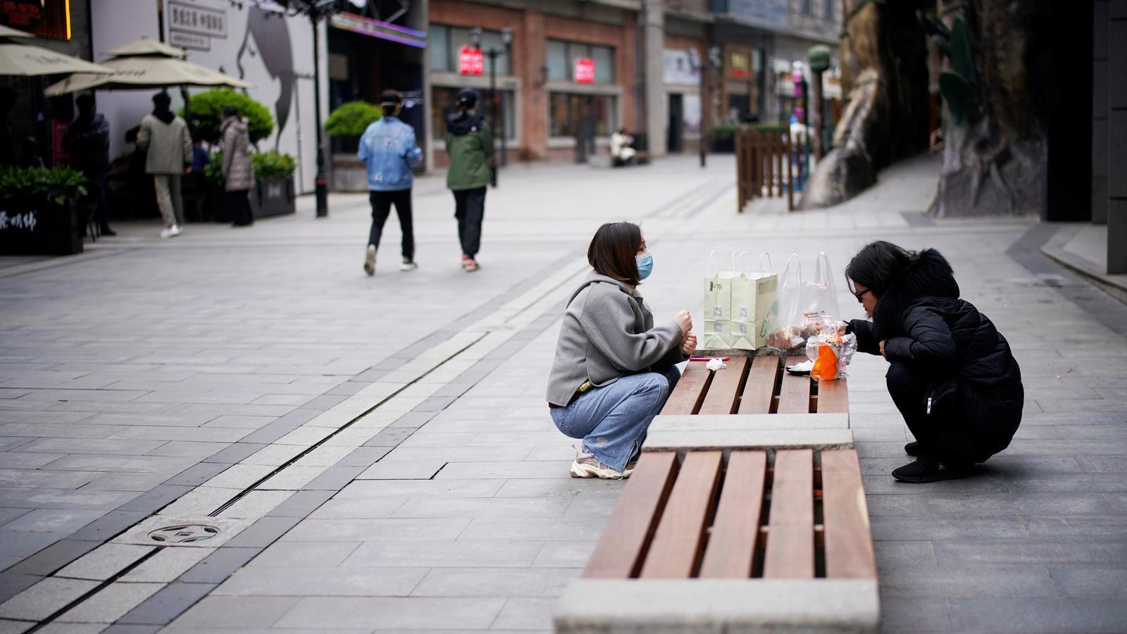 Dues persones mengen en un banc en un carrer comercial de Wuhan, l'epicentre del brot de coronavirus a la Xina que comença a recuperar la normalitat.