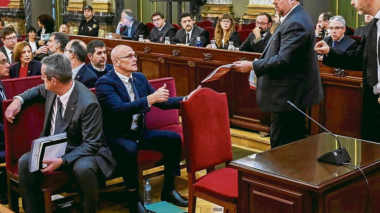 Junqueras donant uns papers de l'advocat Andreu Van den Eynde a Raül Romeva en el primer dia de judici.